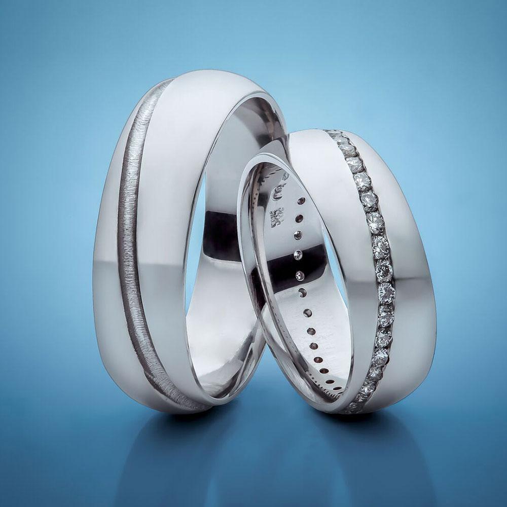 Snubní prsteny z bílého zlata osázené v diagonále bílými diamanty.